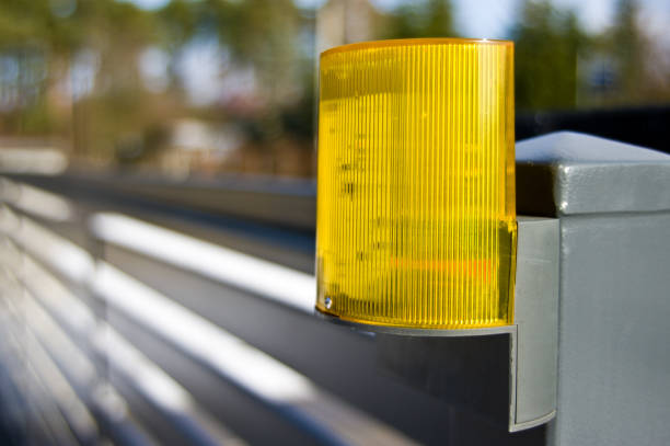 Close-up of a yellow warnig light mounted on driveway gate.